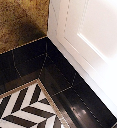Brass liners and solid black marble border the chevron floor mosaic