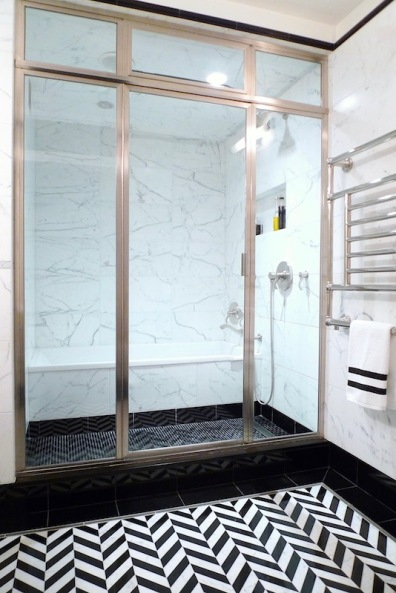 Framed glass shower enclosure with operable transom
