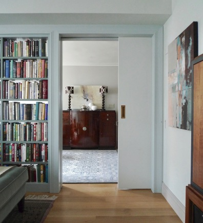 A wide pocket door built into a glass-backed bookcase that replaces a non-structural wall