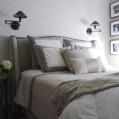 Linen-upholstered headboard in a wallpapered niche