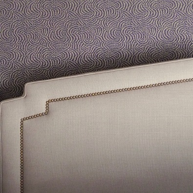 Brass nailheads and gold accents on the plum wallpaper