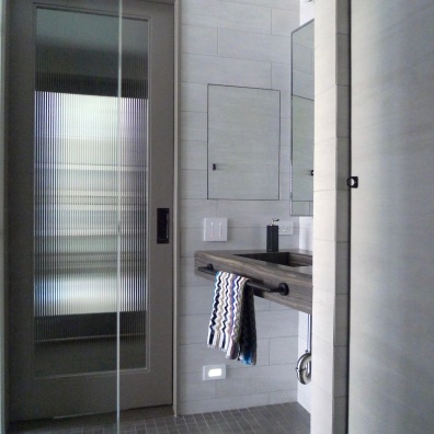 Sink viewed from the glassed-in shower. Storage cabinets are faux-painted to match the wall tile.