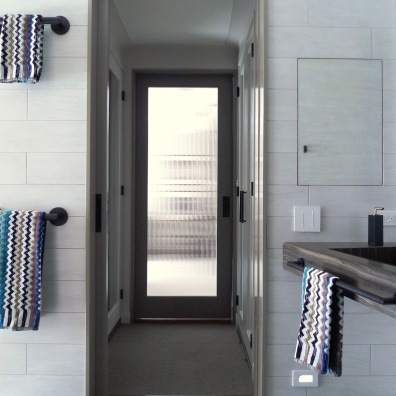Glass doors provide privacy and natural light in the dressing room.