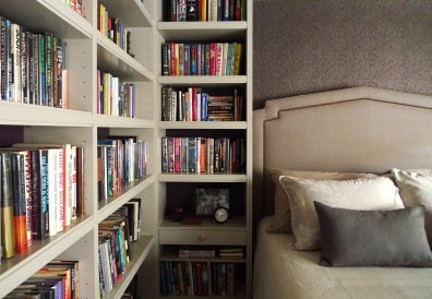 Bookcases wrap all the walls, creating a library bedroom