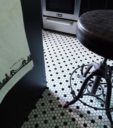 Classic country elements: A black and white hex tile floor and vintage stools.