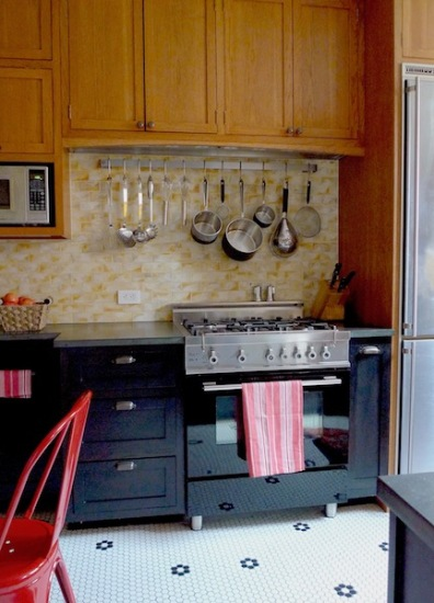 Handmade raku tiles cover the cooking niche, with a long pot rack and black stove that blends with the base cabinets.
