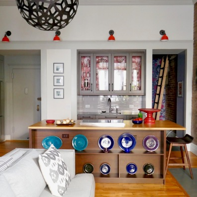 After: The kitchen is moved out into the main space and a wooden frame unifies the doorways