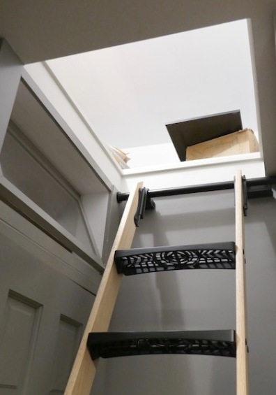 A custom ladder accesses a large storage space created above the new kitchen