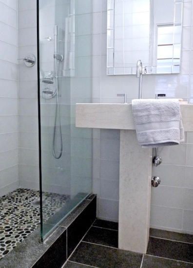 Large scale glass field tiles combine with river rock in the shower and brushed granite on the floor
