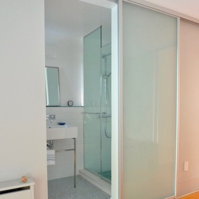 Frosted glass barn door makes the most of this narrow guest bath space