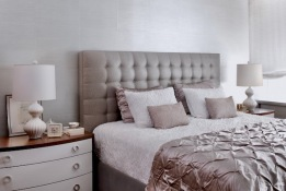 The custom headboard is polished linen. The custom bedside table has a bow front.