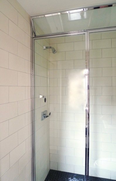 The custom framed shower enclosure . . .