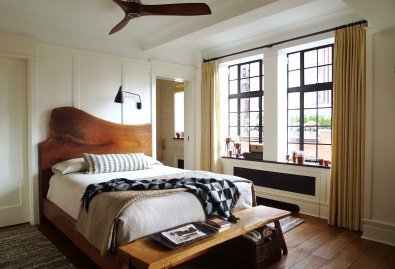 The custom black walnut bed has a live-edge headboard