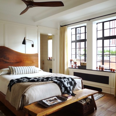 The custom black walnut bed has a live-edge headboard