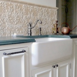 "The handmade bas-relief backsplash tiles are a distinctive element that takes this room beyond the usual ""white kitchen."""