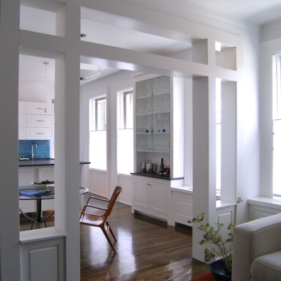 A wide span opened between rooms is framed with support columns in a unique design.