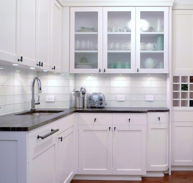 A curved wood door finishes the base cabinet run in a classic white kitchen.