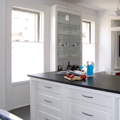 A glass-front cabinet set between two windows shows off barware.