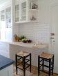 A wood-topped breakfast bar is squeezed into a narrow kitchen.