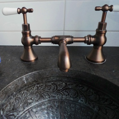 Hand-crafted copper sink with copper bridge faucet