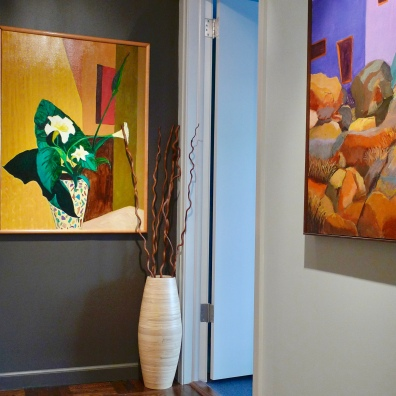 A deep accent wall sets off colorful art.